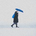 woman in blue coat holding umbrella